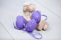 Pretty cuddly woolly toy sheep sitting floor group purple easter eggs Royalty Free Stock Photography