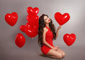 Pretty cute brunette girl in red with heart balloons posing isol Royalty Free Stock Photo