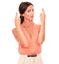 Pretty cute female with crossing fingers gesturing a luck sign and making a wish while looking at you in white background Royalty Free Stock Photos