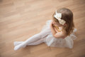 Pretty diligent ballet girl sitting in white tutu at dance studi Royalty Free Stock Photo