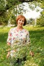 A beautiful elderly woman in flaxen clothes stands tranquilly in her green garden Royalty Free Stock Photo