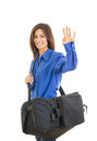 Pretty fashionable woman with large suitcase waving Royalty Free Stock Photo