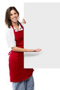 Pretty female chef holding a blank sign white standing alongside it and gesturing with her hand to draw your attention to the Stock Image