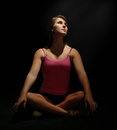 Pretty female dancer sitting cross legged on floor with a black background Stock Photography