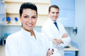 Pretty female dentist portrait of arms crossed with colleague standing in background Stock Image
