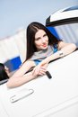 Pretty female driver showing the car key in a white Stock Photos