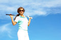 Pretty female golfer relaxing holding ball and golfclub against clear blue sky Stock Image