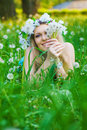 Pretty female lying down in the meadow of spring flowers Royalty Free Stock Photos