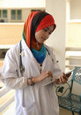 Pretty female Muslim doctor with stethoscope. Stock Photos