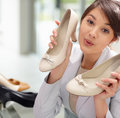 Pretty female shopping for a pair of shoes Stock Photos