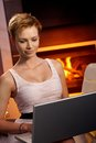 Pretty female using laptop by fireplace Stock Images