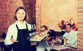 Pretty female waiter showing country restaurant Royalty Free Stock Photo
