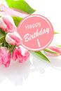 Pretty feminine happy birthday greeting with a festive pink rosette and a bouquet of beautiful fresh pink tulips on a white Royalty Free Stock Photo