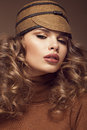 Pretty fresh girl image of modern twiggy in fashionable brown hat with unusual eyelashes and curls photos shot studio Stock Image