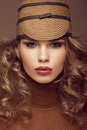 Pretty fresh girl image of modern twiggy in fashionable brown hat with unusual eyelashes and curls photos shot studio Royalty Free Stock Photo