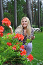 Pretty gardener woman with red flower bush Stock Photo