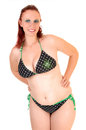 Pretty girl in bikini a lovely teen a black and green with red hair standing for white background smiling Royalty Free Stock Image