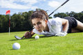 Pretty girl cheating on golf field tried to push the ball with her finger Stock Photography