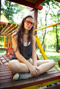 Pretty girl on climbing frame in park with sunglasses sitting Stock Images