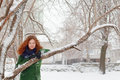 Pretty girl clings to tree outdoor at winter day in blue scarf in park Royalty Free Stock Photography