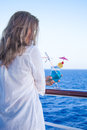Pretty girl with a cold drink admiring the sea views summer Stock Photo