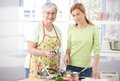 Pretty girl cooking with senior mother smiling Stock Image