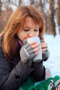 Pretty girl drinking tea in winter park Stock Image