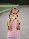 A pretty girl is eating a cheeseburger on a blurred street background. A little girl with a sandwich. Royalty Free Stock Photo