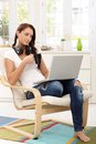 Pretty girl enjoying leisure time with laptop and a cup of tea in living room armchair Royalty Free Stock Images