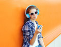 Pretty girl enjoys listen to music in headphones and using smartphone against the colorful orange wall Stock Photo