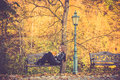 Pretty girl in fall reading blond a book on a park bench or autumn background Stock Photography