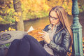 Pretty girl in fall reading blond a book on a park bench or autumn background Royalty Free Stock Photos
