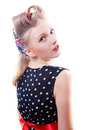 Pretty girl funny young blond pinup woman in polka dot dress with curlers looking at camera shoulders back isolated on white backg Royalty Free Stock Photo
