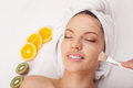 Pretty girl is getting skin care treatment attractive young woman having facial clay mask at spa she lying and smiling the lady Stock Images