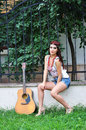 Pretty girl with a guitar outdoors young slender woman Royalty Free Stock Image