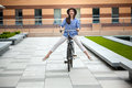 Pretty girl in hat riding a bicycle at street Royalty Free Stock Photo