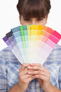 Pretty girl hiding face with colour charts on white background Stock Photos