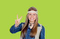 Pretty girl with hippie clothes making the peace symbol on green background Royalty Free Stock Images