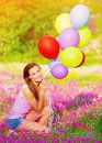 Pretty girl holding colorful balloons sitting down on pink floral meadow and in hands having fun outdoors summer vacation concept Stock Image