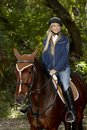 Pretty girl horseback riding blonde in the woods Stock Photos