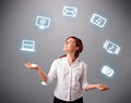 Pretty girl juggling with elecrtonic devices icons standing and Royalty Free Stock Image
