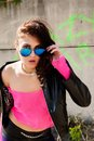 Pretty girl in leather jacket young beautiful woman sunglasses at wall background Stock Image