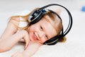 Pretty girl listening to music on headphones with lying the floor in the living room Royalty Free Stock Images