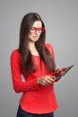 Pretty girl looking at pad tablet pc screen in red glasses studio shot on gray background Stock Image