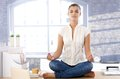 Pretty girl meditating on top of desk Royalty Free Stock Image