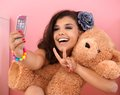 Pretty girl photographing herself and toy bear Royalty Free Stock Image
