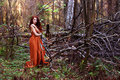 Image : Pretty girl in plaid stands near downed trees in forest  hunter a