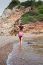 Pretty girl posing on the beach attractive brunette in purple swimsuit rocky greek island evia captured from behind walking along Royalty Free Stock Photo