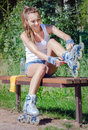 Pretty girl putting on inline skates sitting the bench and Royalty Free Stock Image
