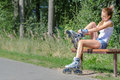 Pretty girl putting on inline skates sitting the bench and Stock Photo